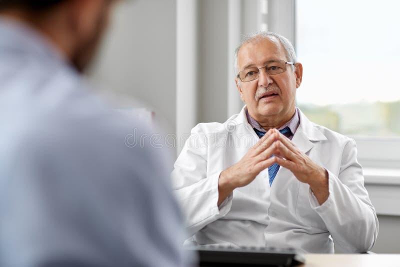 Doctor mayor que habla con el paciente masculino en el hospital imagen de archivo