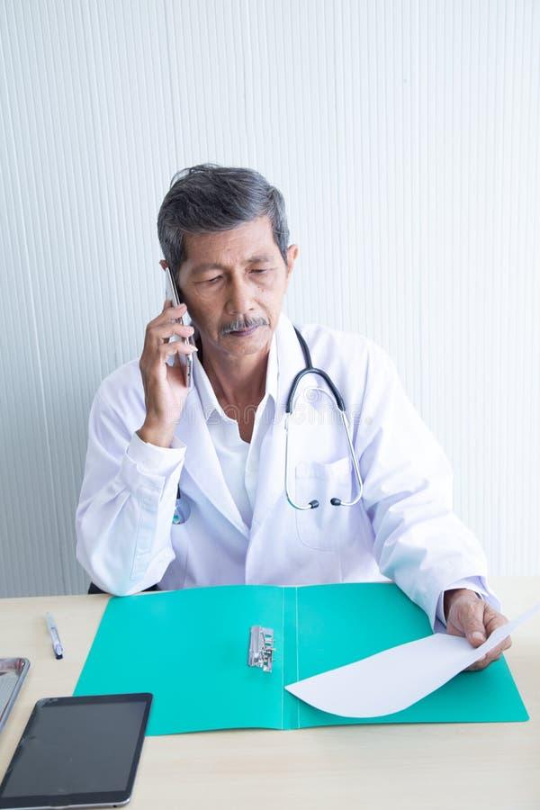 Doctor mayor que habla el teléfono móvil y el documento leído imagen de archivo libre de regalías