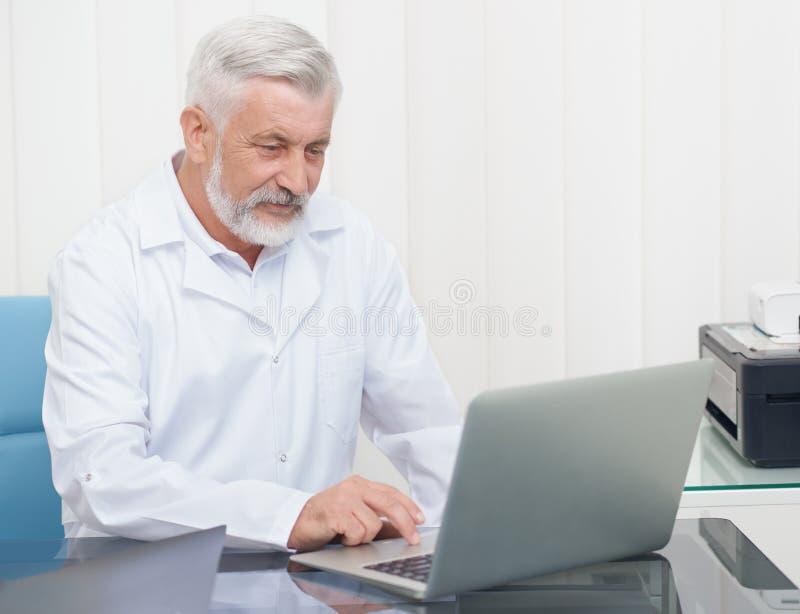 Doctor mayor que lleva en el uniforme blanco que trabaja con el ordenador portátil imagenes de archivo