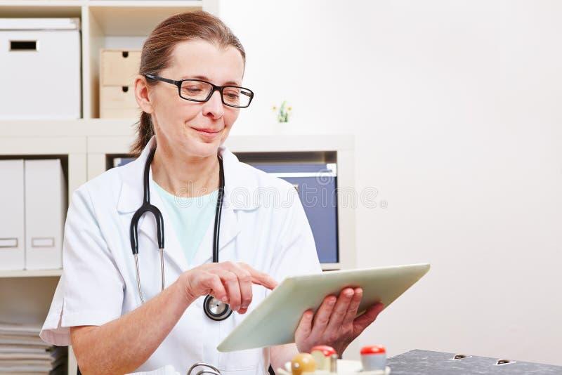 Doctor mayor que usa el ordenador de la tablilla imagenes de archivo