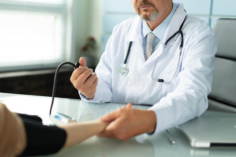 A doctor measures the blood pressure of a patient stock photo
