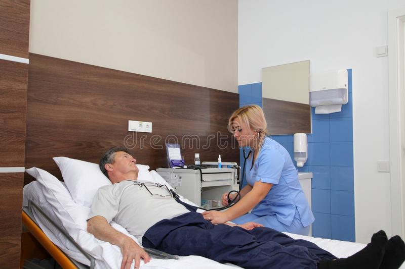 The doctor measures the blood pressure of the patient. royalty free stock photography