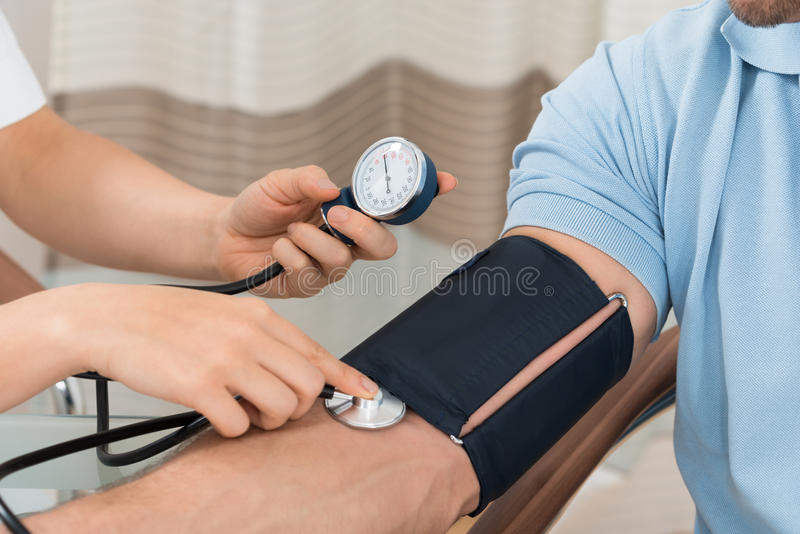 Doctor measuring blood pressure of male patient royalty free stock image