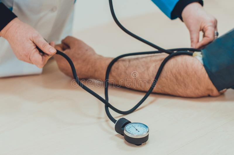 A doctor measuring blood pressure of a male patient with sphygmomanometer and stethoscope royalty free stock photography