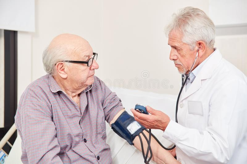 Doctor measuring blood pressure at an old man. Doctor measuring blood pressure in an old men as a control in hypertension royalty free stock image
