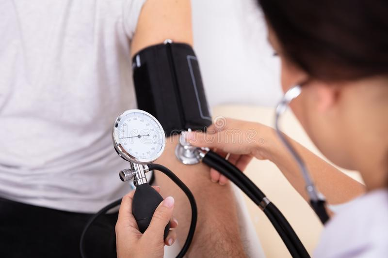 Doctor Measuring Blood Pressure Of Patient stock images