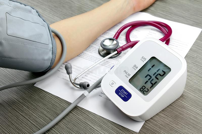 Doctor measuring blood pressure of patient. stock photography