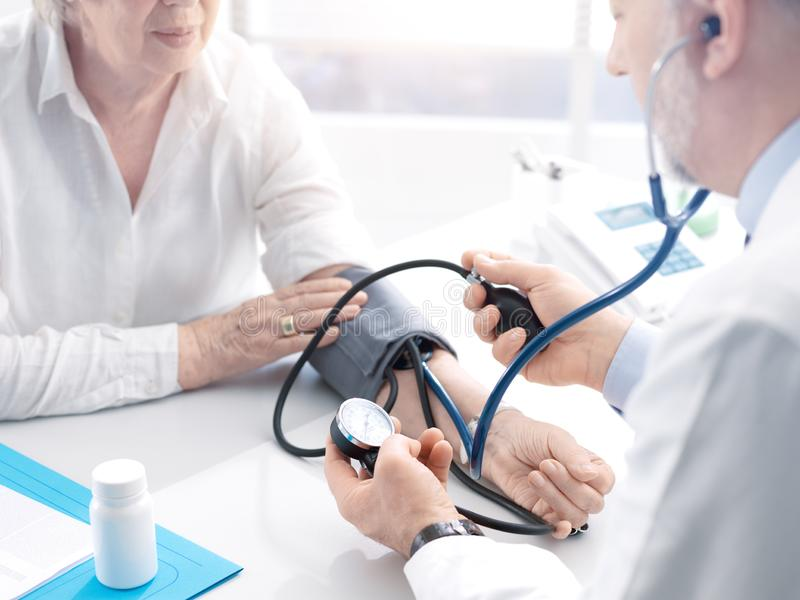Doctor measuring blood pressure of a senior patient royalty free stock image