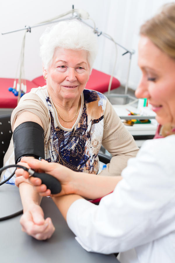 Doctor measuring blood pressure of senior patient royalty free stock image
