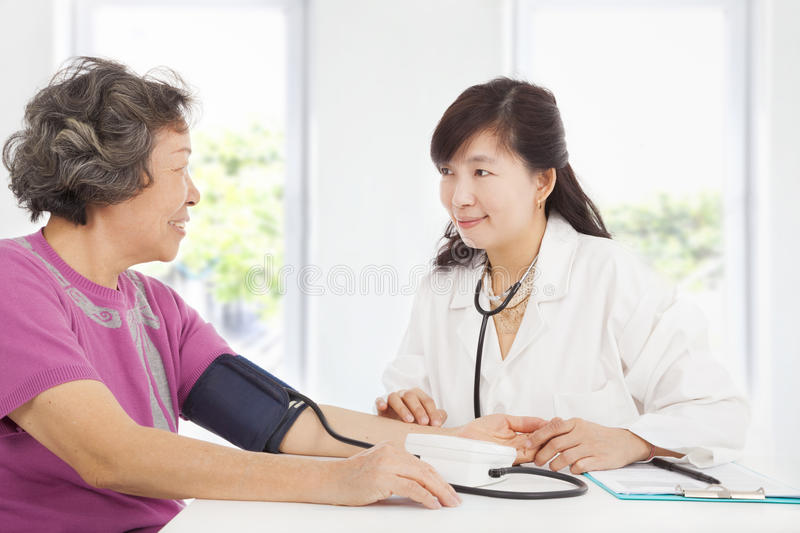 Doctor measuring blood pressure of senior woman stock images