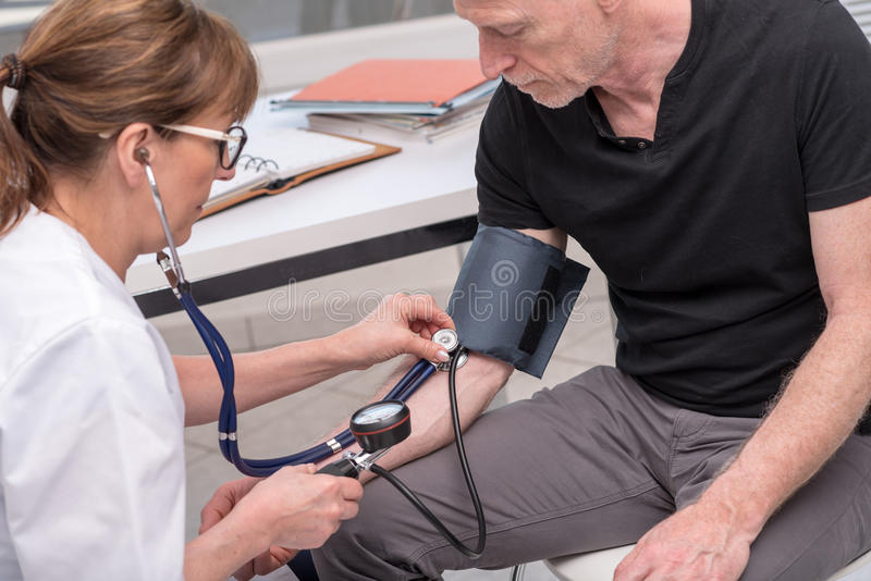 Doctor measuring blood pressure with sphygmomanometer royalty free stock photo