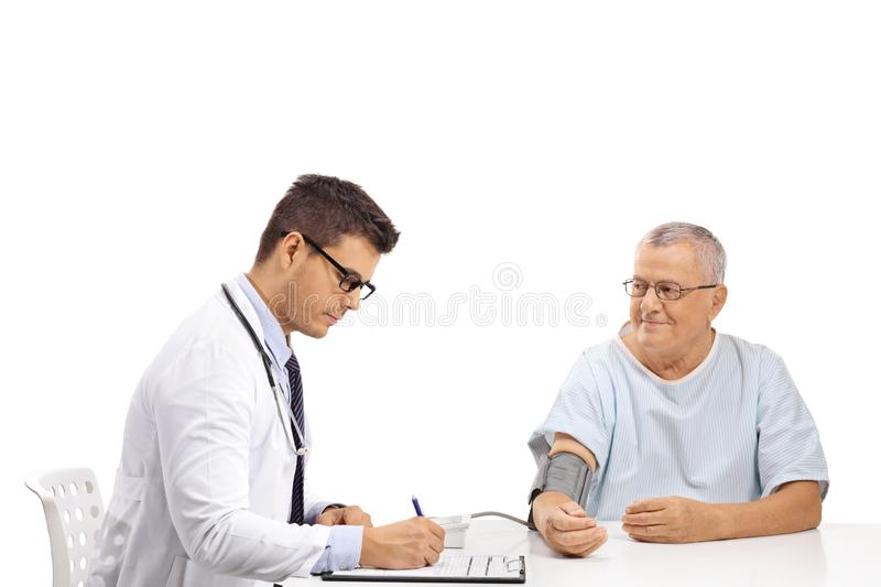 Doctor measuring blood pressure to a mature male patient royalty free stock photo