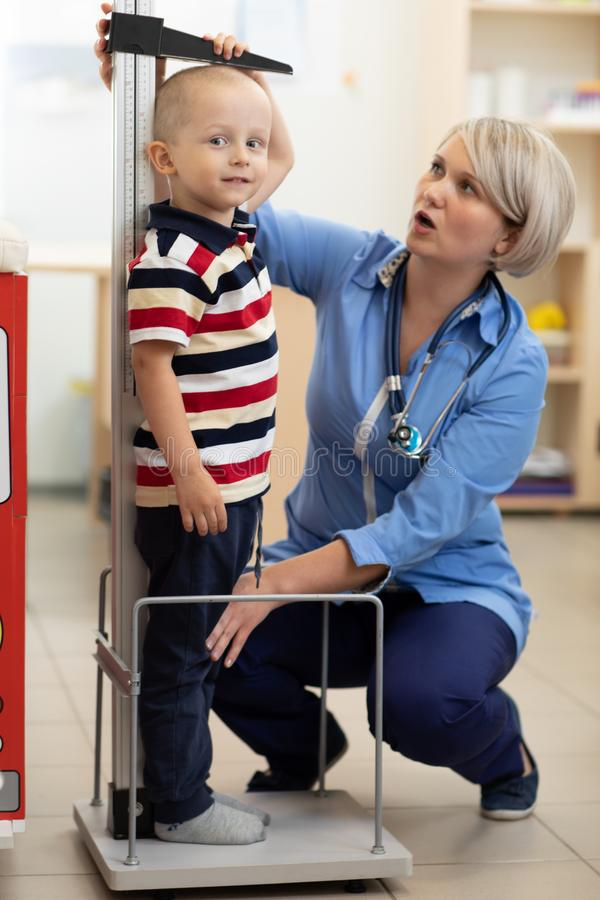 Doctor measuring boy`s height royalty free stock image