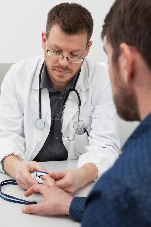 A doctor measuring with a pulse oximeter. A doctor measuring oxygen saturation and heart rate with a pulse oximeter stock image