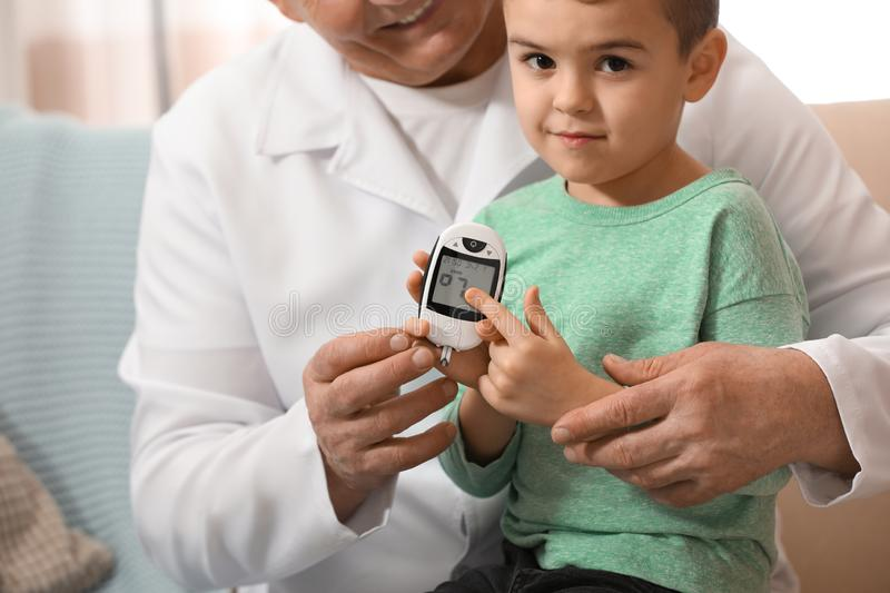 Doctor measuring patient`s blood sugar level with digital glucose meter at home, closeup. Diabetes control royalty free stock images