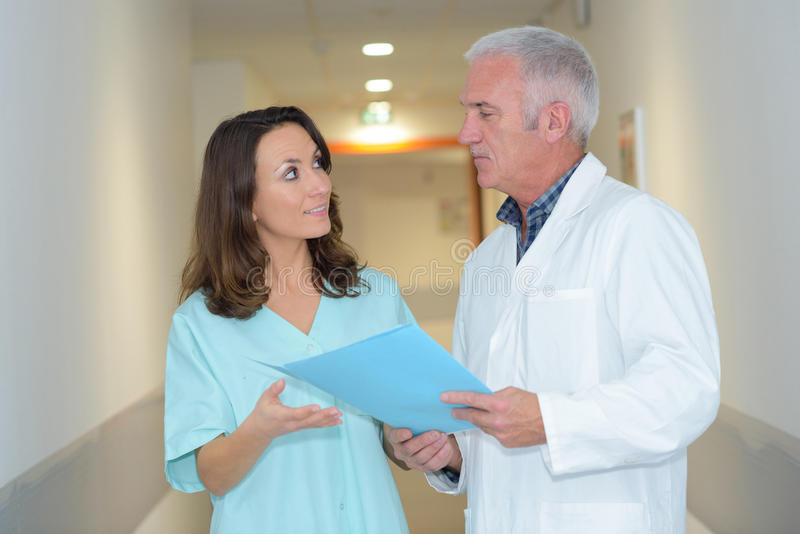 Doctor and medical assistant having conversation. Doctor and medical assistant having a conversation royalty free stock photo