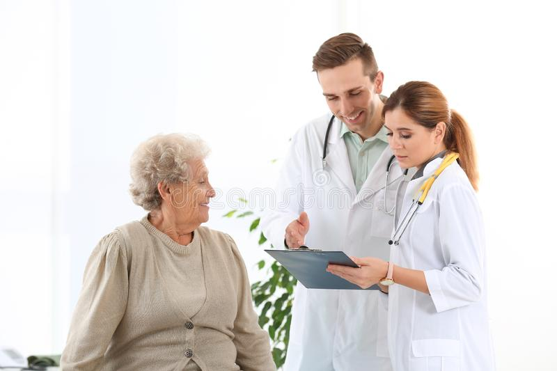 Doctor and medical assistant working with elderly patient royalty free stock photo