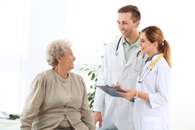Doctor and medical assistant working with elderly patient. In hospital royalty free stock photos