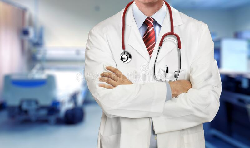 Doctor in medical coat with arms crossed in the hospital ward royalty free stock photo