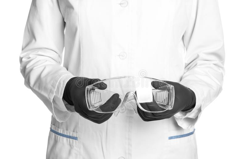Doctor in medical gloves holding safety glasses royalty free stock photography