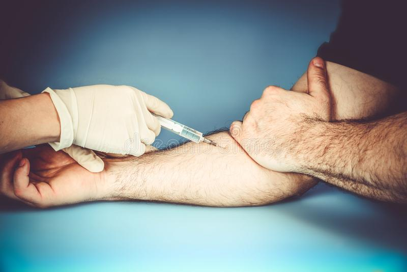 The doctor in medical gloves makes an injection intravenously to the patient during treatment to prevent the disease stock images