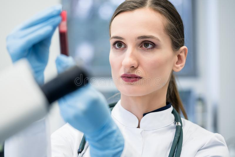 Doctor in medical laboratory looking at blood test. She is holding in her hand royalty free stock photo