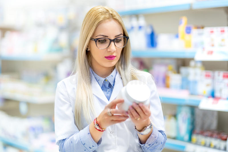 Doctor, medical nurse and pharmacist reading the drug label in pharmacy royalty free stock photos