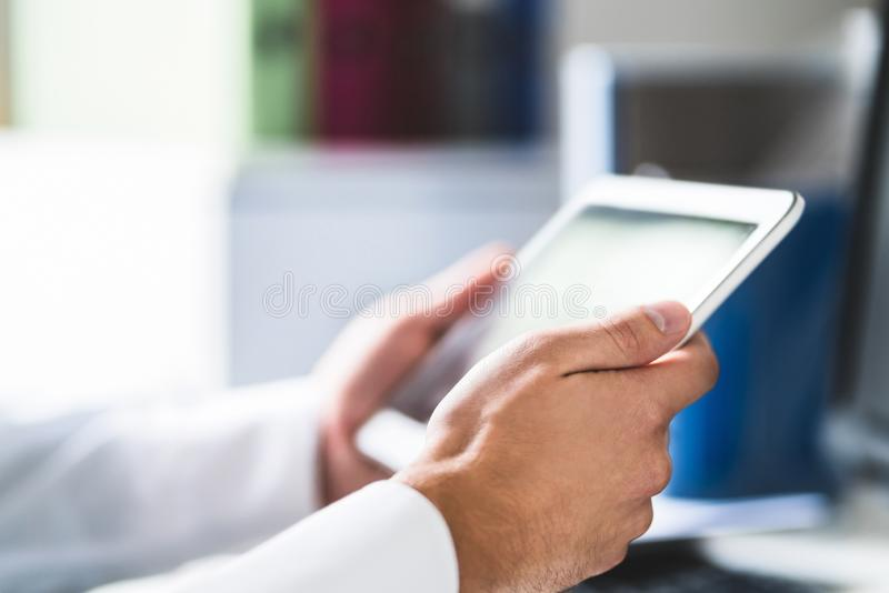 Doctor and medical professional using tablet at work in health care. royalty free stock photo