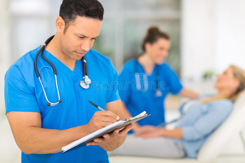 Doctor medical report. Professional middle aged doctor writing medical report royalty free stock image