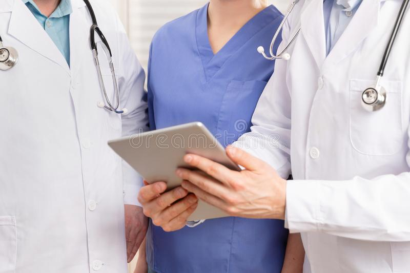 Doctor and medical team discussing patient report at tablet computer in hospital stock photo