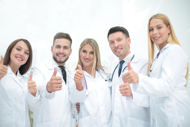 Portrait of a doctor and medical team showing thumb up. Doctor and medical team showing thumb up.the concept of teamwork stock image