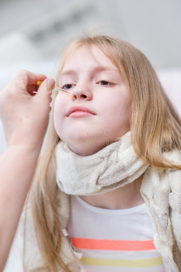 Doctor medication drips into the nose girl.  stock photos