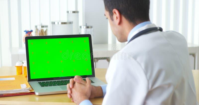 Doctor mexicano que habla con el ordenador portátil con la pantalla verde foto de archivo libre de regalías