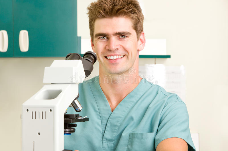 Doctor with Microscope. A doctor looking through a microscope royalty free stock photos