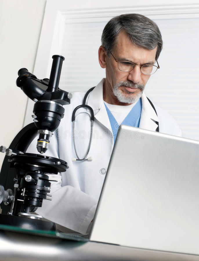 Doctor with Microscope and Laptop Computer. A doctor researching at the microscope and laptop computer stock images