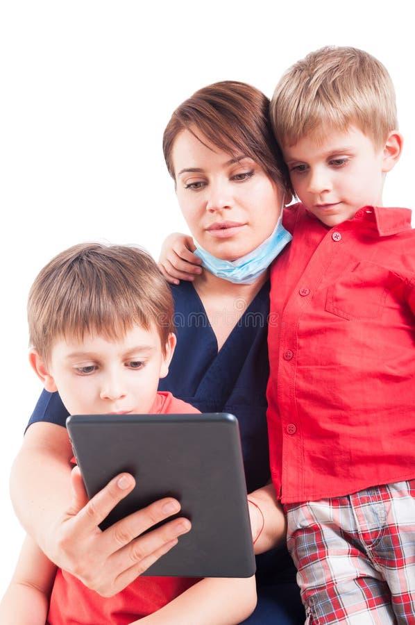 Doctor moderno de la mujer que usa la tableta con los pacientes del niño fotos de archivo
