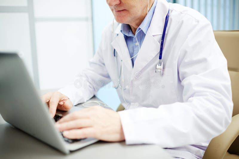 Doctor moderno que usa el ordenador portátil en oficina imágenes de archivo libres de regalías