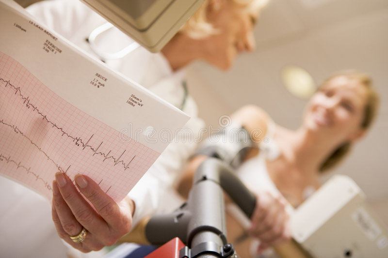Doctor Monitoring Female Patient On Treadmill stock image