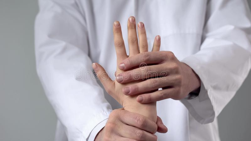 Doctor moving patient wrist, first aid in clinic, assessing severity of injury royalty free stock images