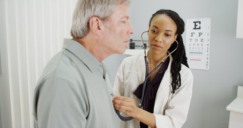 Doctor negro que escucha la respiración mayor imagen de archivo libre de regalías