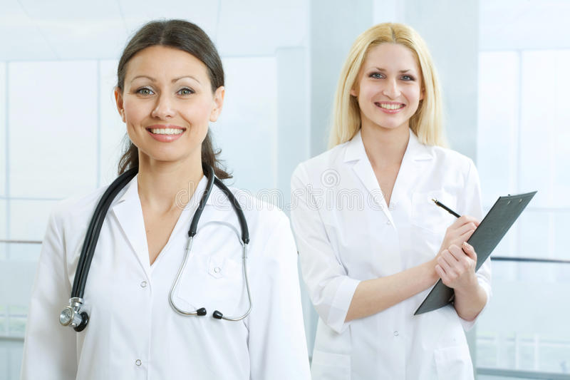 Doctor and nurse. Portrait of doctor with stethoscope and nurse writing something stock images