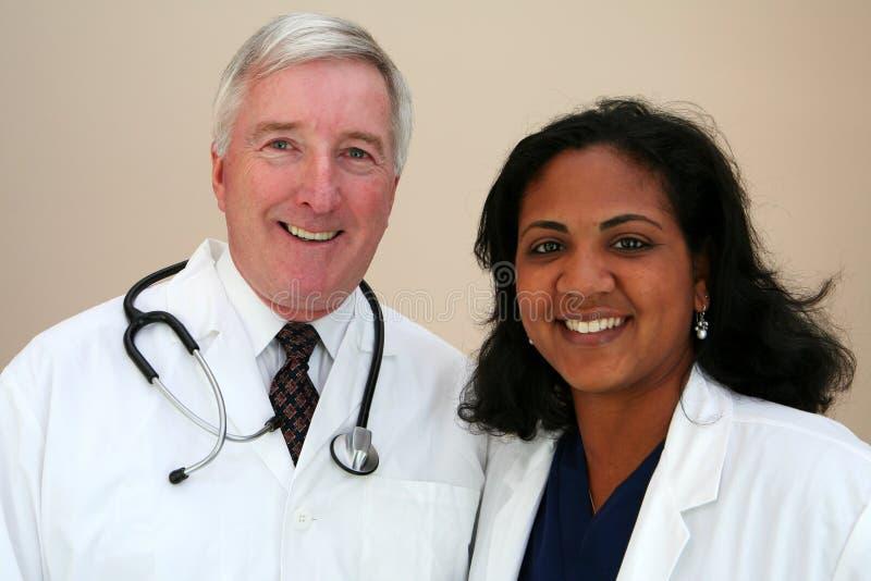 Doctor and Nurse. Caucasian Doctor with minority Nurse stock image