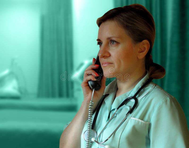 Doctor or nurse call by phone. Woman in uniform with handset and stethoscope around neck speaks consulting royalty free stock images