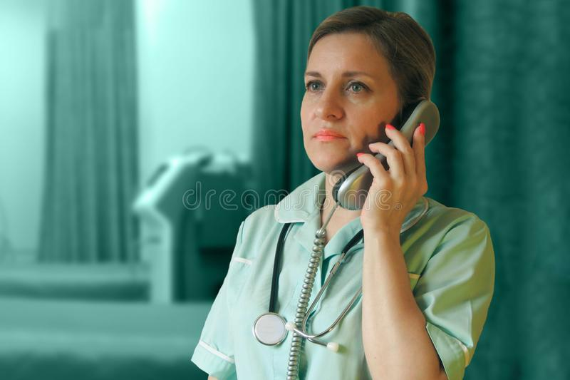 Doctor or nurse call by phone. Woman in uniform with handset and stethoscope around neck speaks stock images