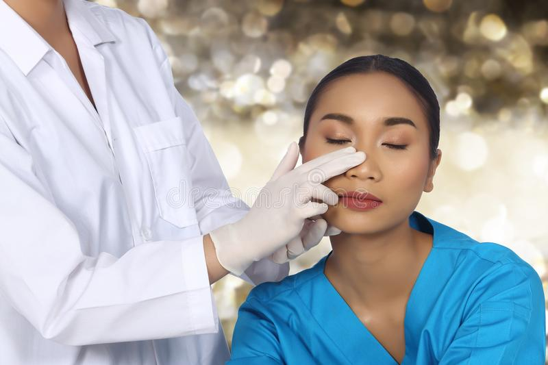 Doctor Nurse check face nose structure before plastic surgery. And inject beauty chemical syringe to Asian Woman tanned skin patient with warm care, copy space royalty free stock image