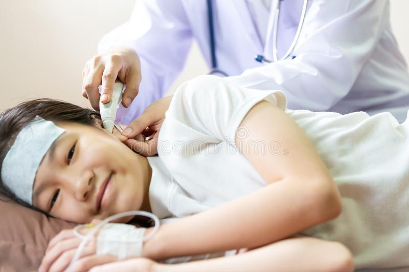 Doctor or nurse checking child patient temperature in the ear using digital thermometer,asian little girl having fever using cold stock photo