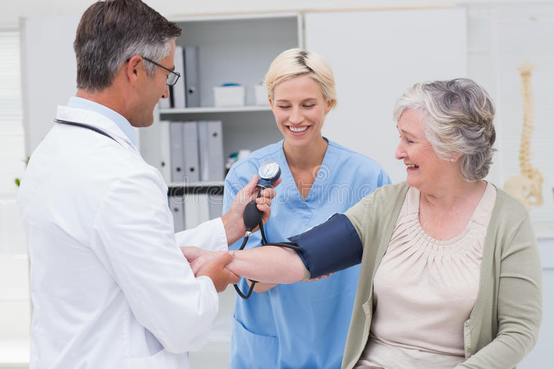 Doctor and nurse checking senior patients blood pressure. Happy doctor and nurse checking senior patients blood pressure in clinic royalty free stock photography