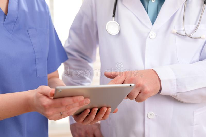 Doctor and nurse discussing patients tests at tablet computer in hospital. Doctor and nurse discussing tests or x-ray image about a patient at tablet computer in royalty free stock image