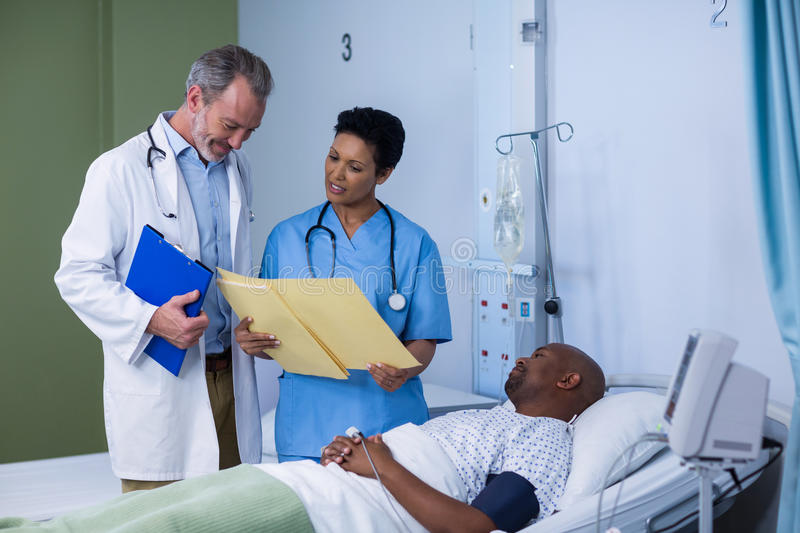 Doctor and nurse discussing report during visit in ward stock photos