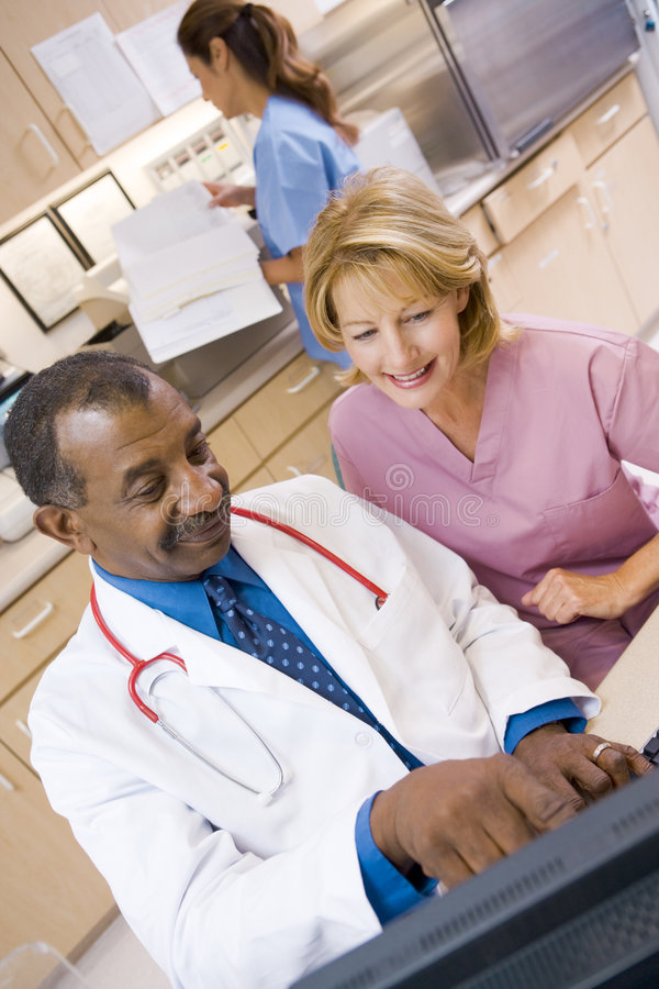 A Doctor And Nurse Discussing Something. At The Reception Area Of A Hospital stock images